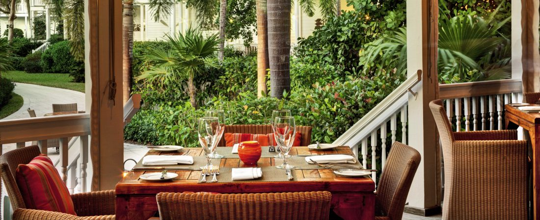 An outdoor dining area surrounded by tropical foliage.