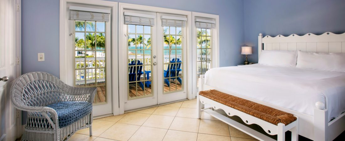 A guest room with a glass panel doors that open to a private porch.
