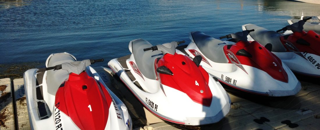Red and white jet skis docked along the water.