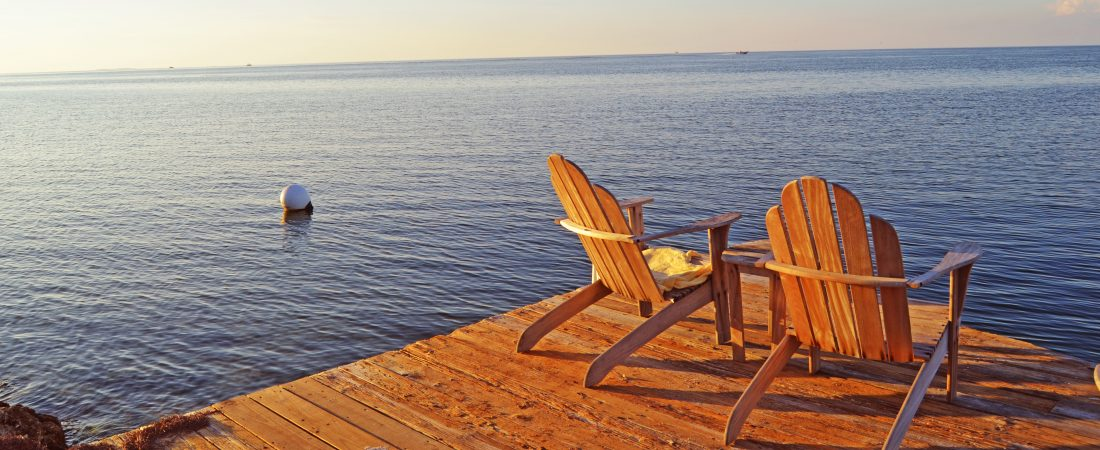 Wooden Adirondack chairs on the edge of a dock.