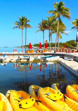 Water sport rentals at Tranquility Bay, including bright yellow ocean kayaks in the foreground.