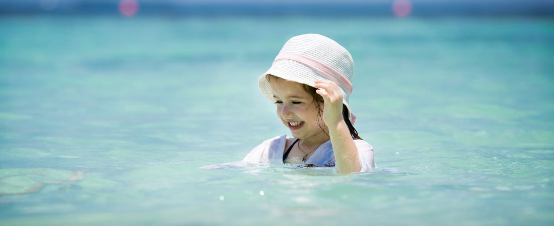 Young girl enjoying swimming in the ocean